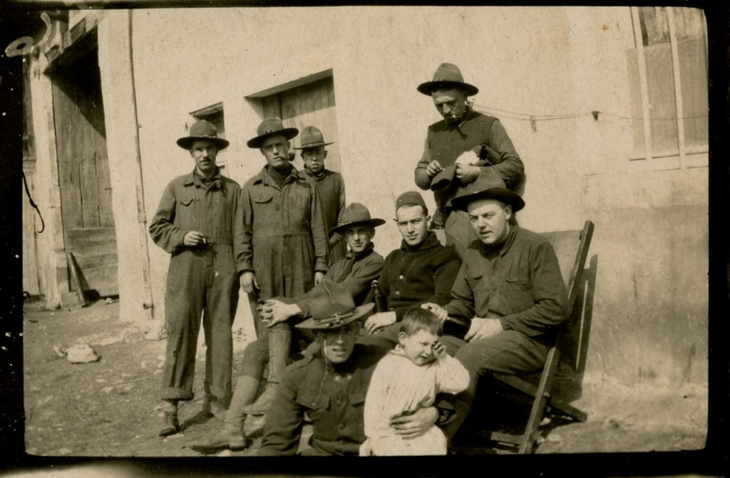 Outdoor casual group photo of soldiers with young boy