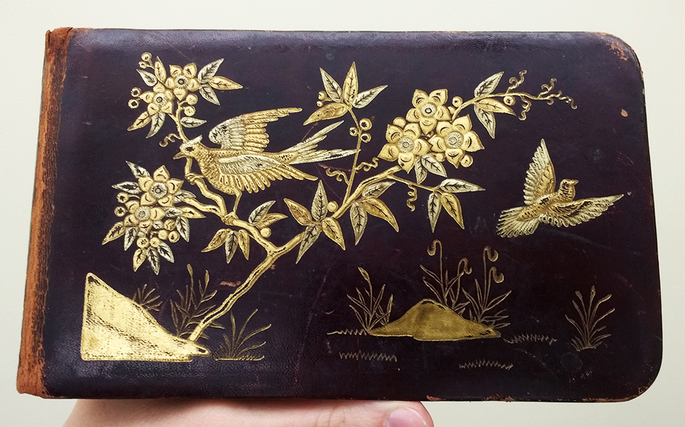 Cover of autograph book, with gold-colored birds and flowers on it