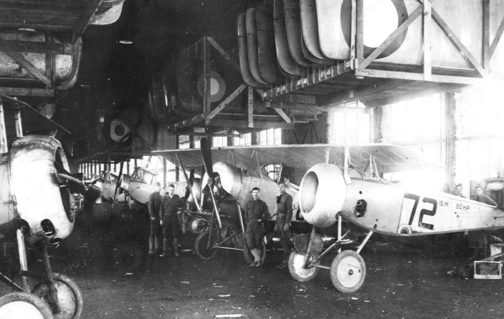 Men standing in front of rows of airplanes, in hangar