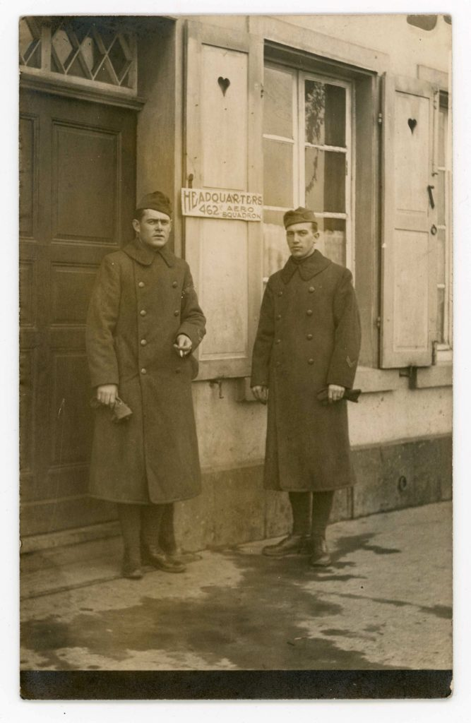 Two men standing in front of door marked 462 Aero Squadron Headquarters