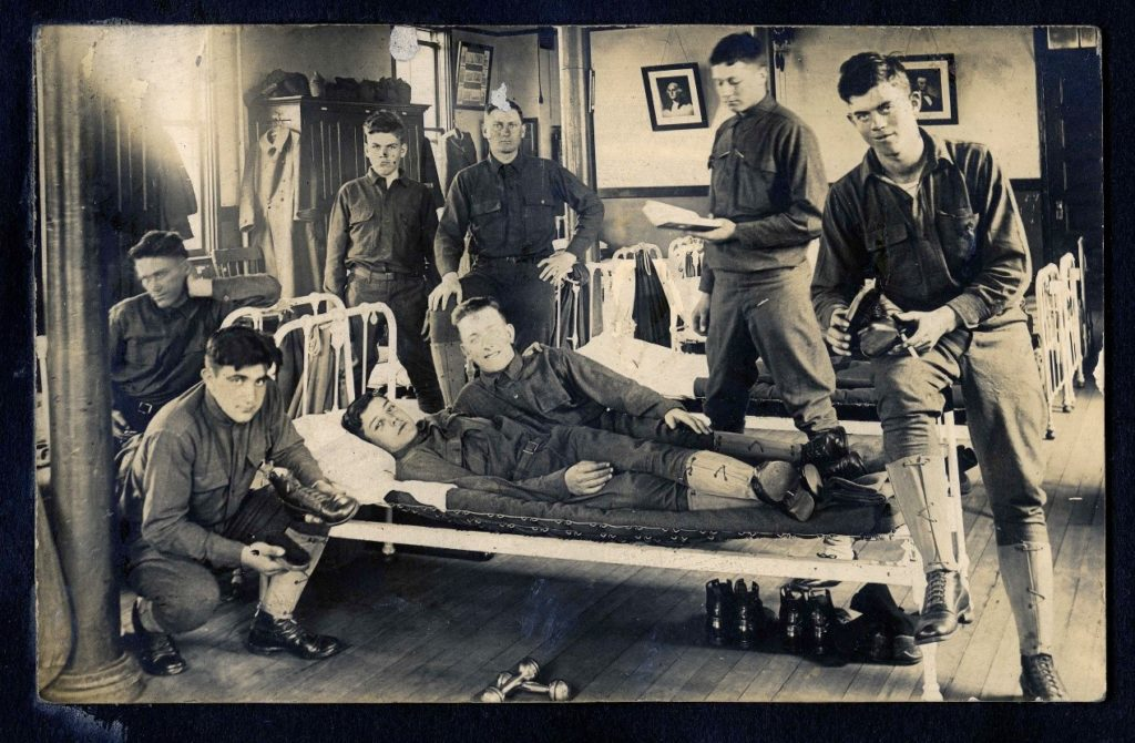 Group of soldiers posed on and around a bed in a barracks