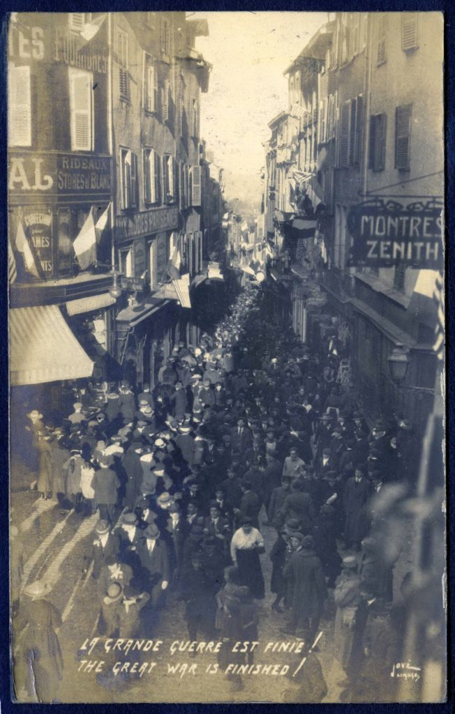 "Postcard showing a crowd of people filling a French city street, with the text in English and French, ""The Great War is Finished!"""