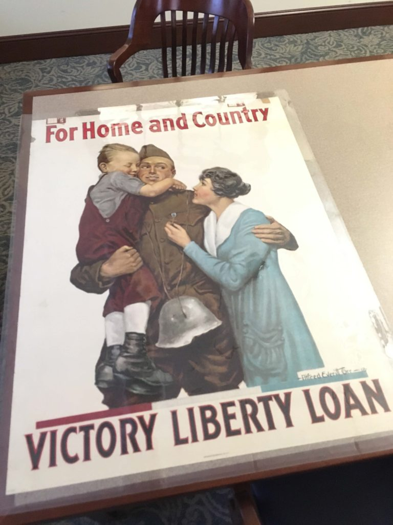 On a table, Poster of soldier, child, and wife, saying For Home and Country, Victory Liberty Loan