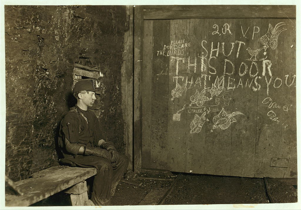 Boy sitting in front of a mine door with writing and images on it