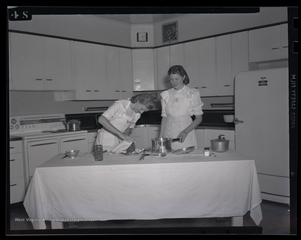 Two women in a kitchen demonstrating bean canning
