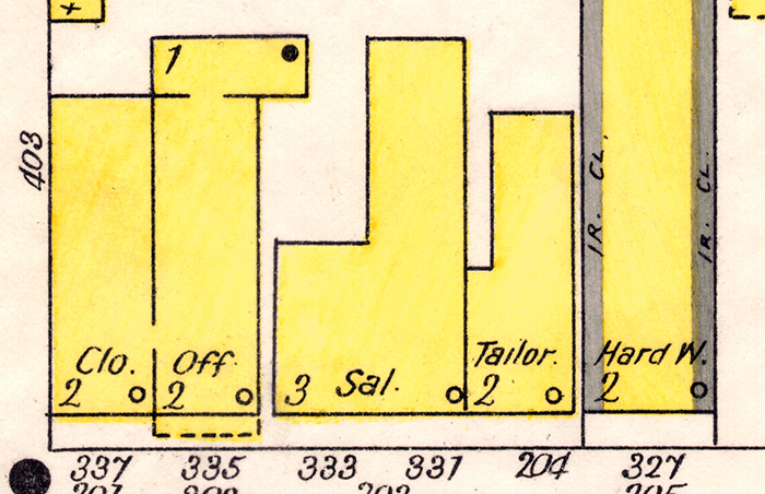 Close-up view of a Sanborn map, showing yellow shaded buildings with shorthand labels regarding their function