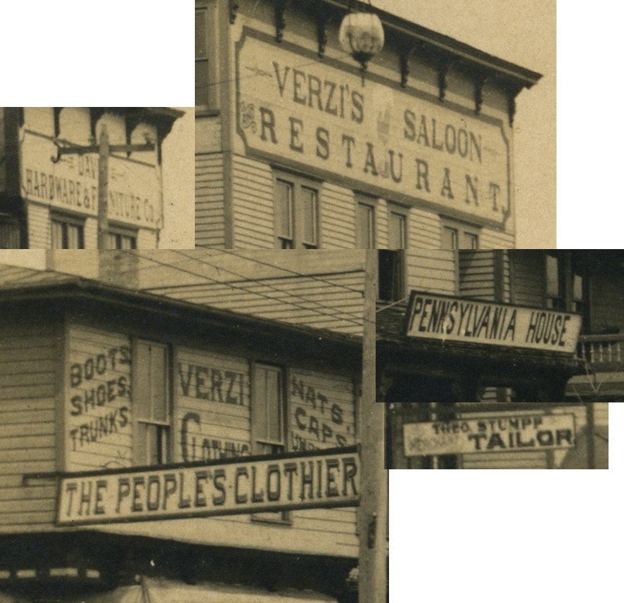 "Signs on buildings, including ""verzi's saloon"" and ""the people's clothier"""
