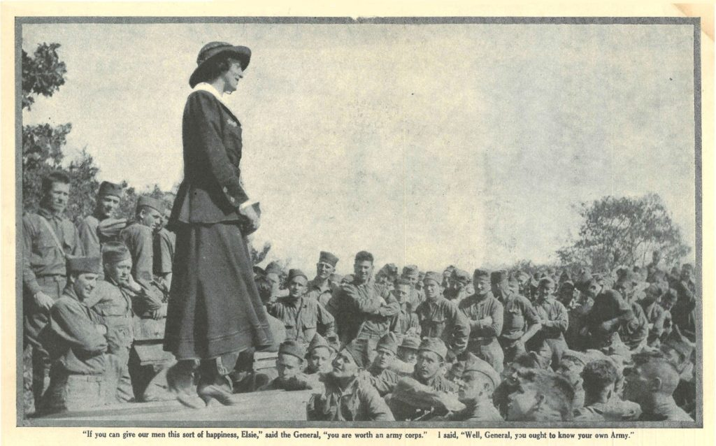 Photo of Elsie Janis standing in front of a group of soldiers