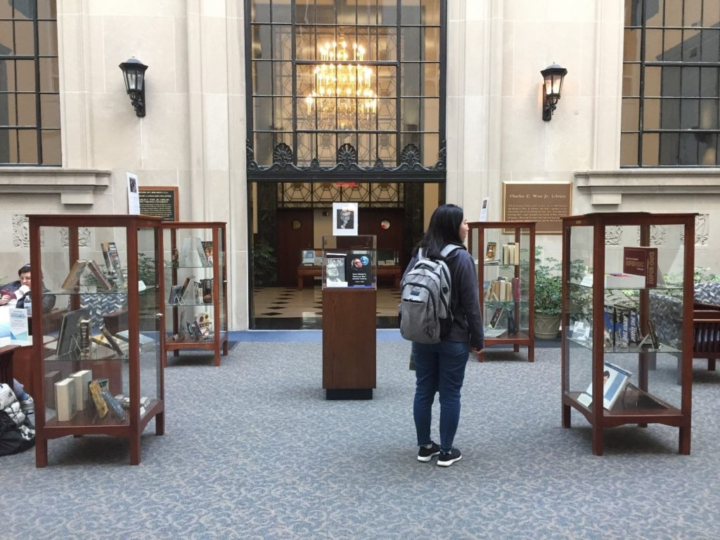 Student viewing Isaac Asimov materials in glass cases in the library atrium