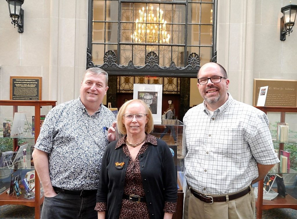 Group photo of Andy Duncan, Stewart Plein, and Dr. Jay Cole in front of the Isaac Asimov exhibit.