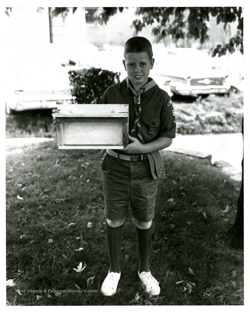 Boy scout holding bird feeder