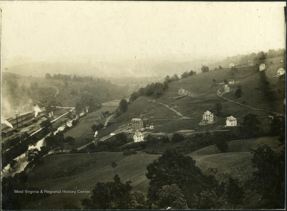 Image of hillsides dotted with a few houses, and a factory at the bottom.