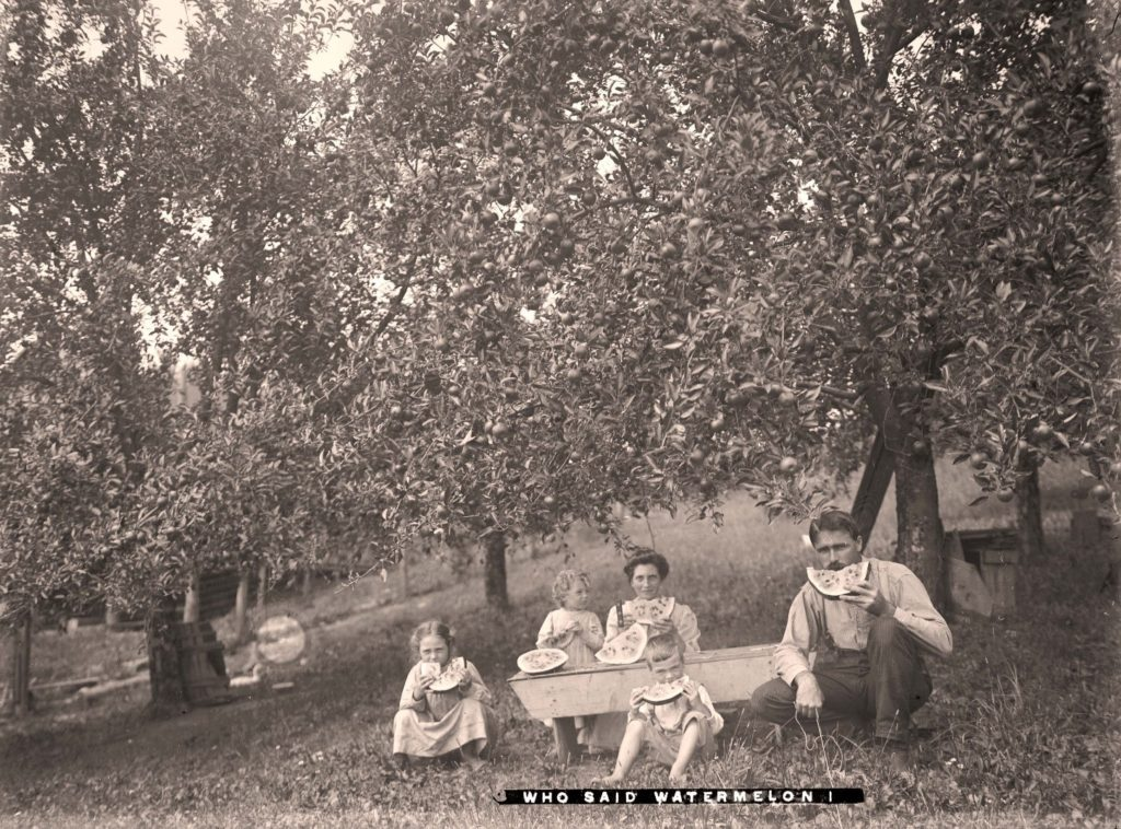 "Family seated outside eating watermelon in an orchard, with text ""Who Said Watermelon!"""