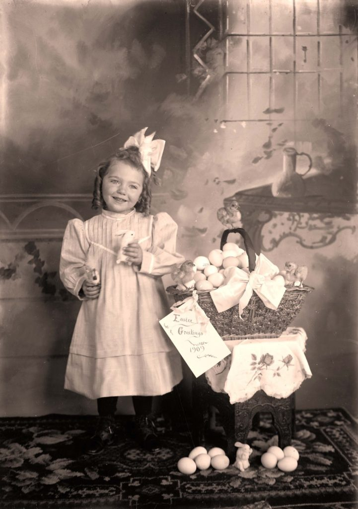 Girl in Easter dress, holding a toy bunny, next to an Easter basket