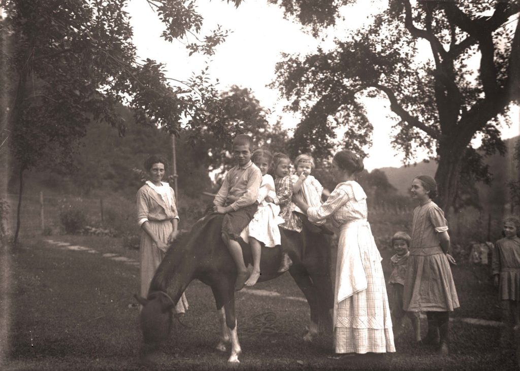 Four children seated on a horse or mule, surrounded by family members