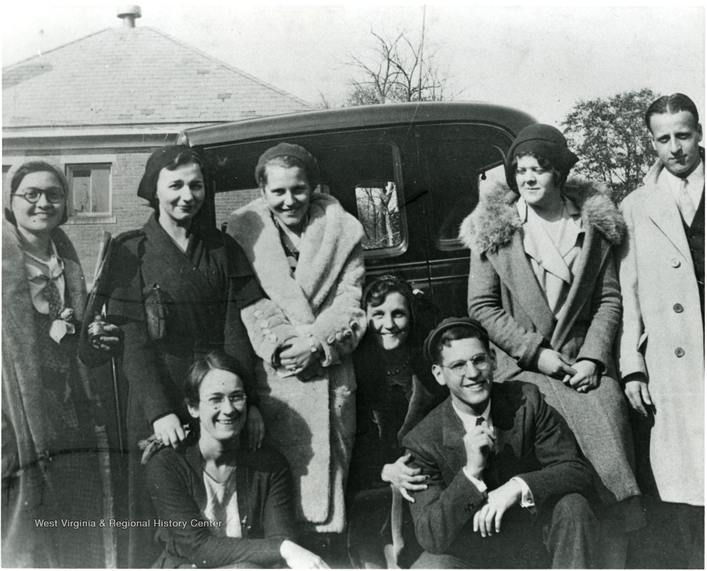 Group of well-dressed men and women posed in front of a car