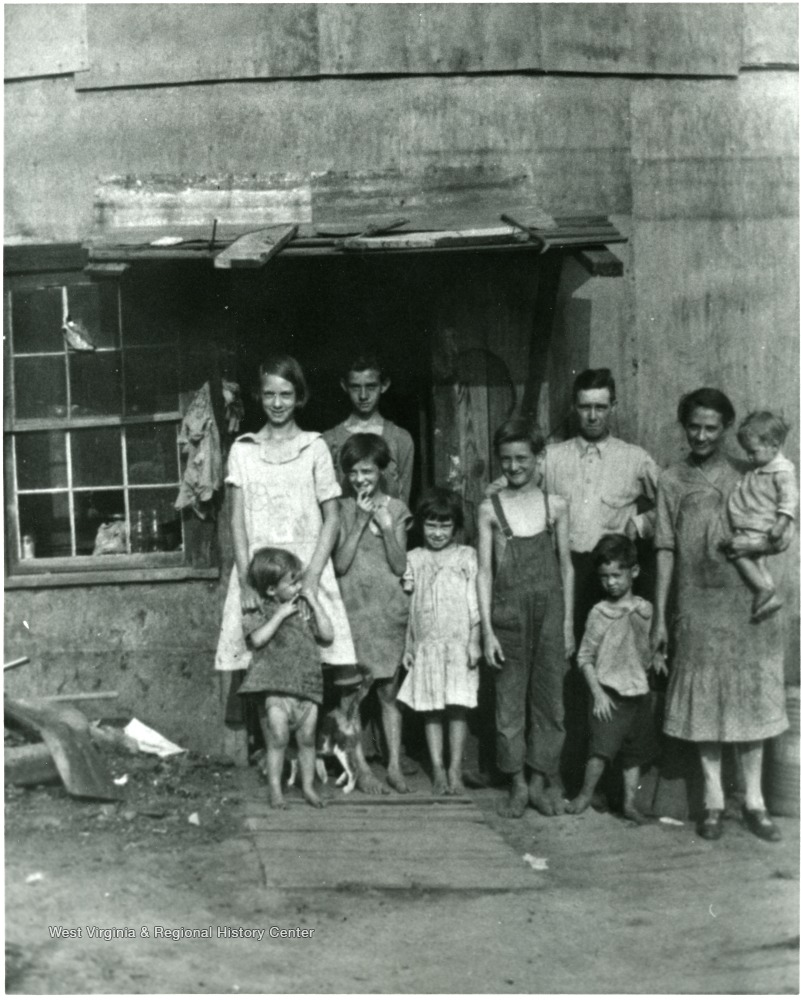 Family posed outside of a building; two parents, eight children, and a pet.
