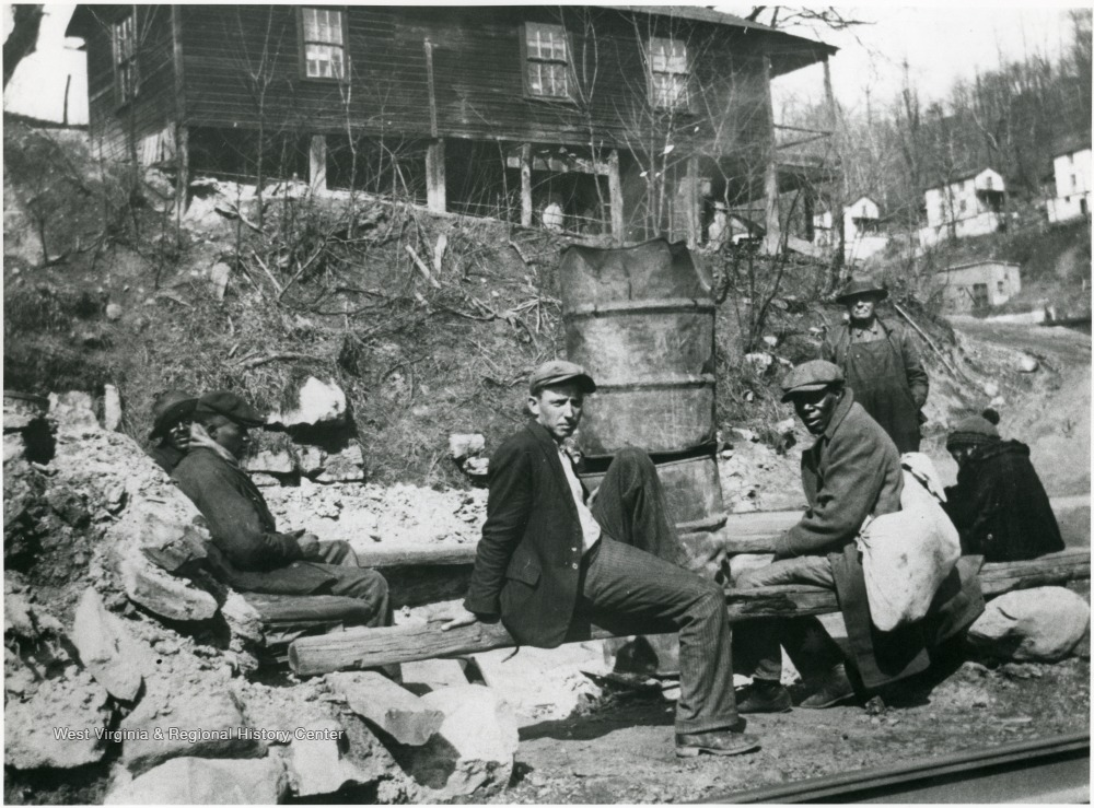 African-American and white men seated on log benches in front of a house.