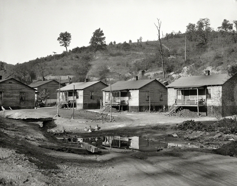 Row of wooden homes with front porches, belonging to coal miners, along a dirt road