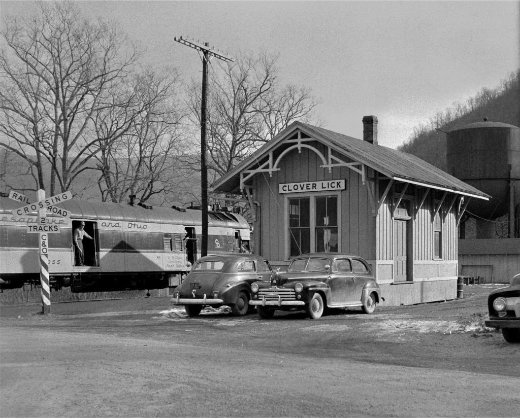 Image of Chesapeake and Ohio train beside small train depot in Clover Lick, WV.