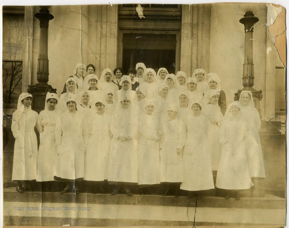 Red Cross nurse group photo, with women standing outside in white nursing uniforms