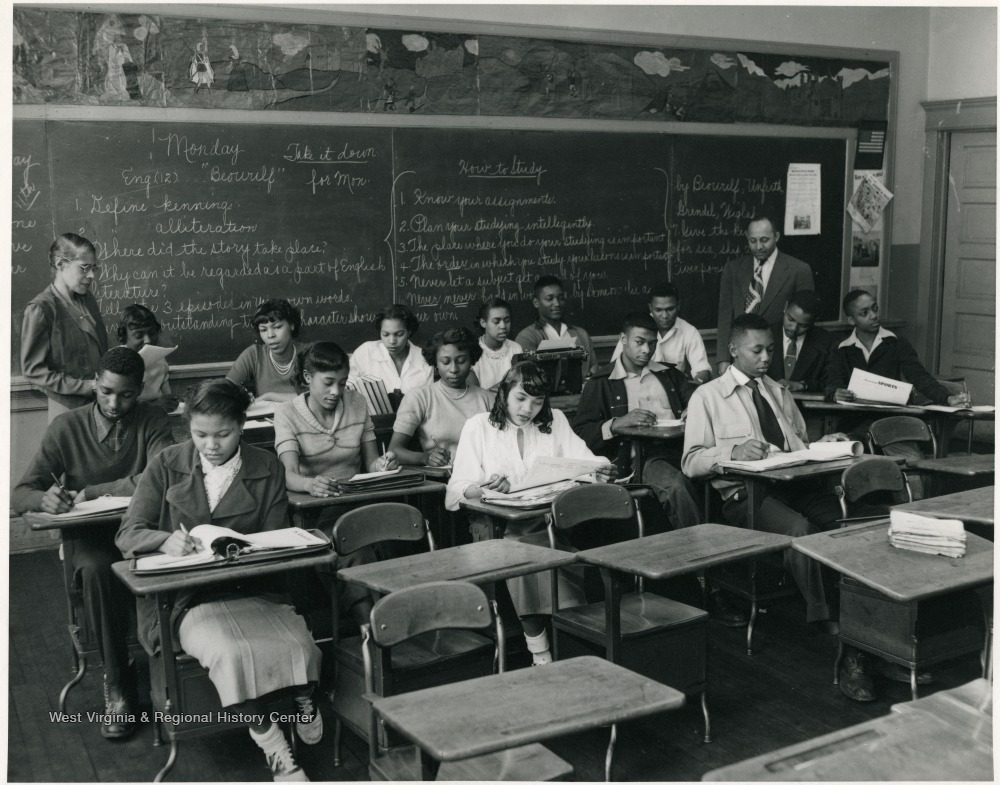 Students seated at desks in a classroom as teachers look on