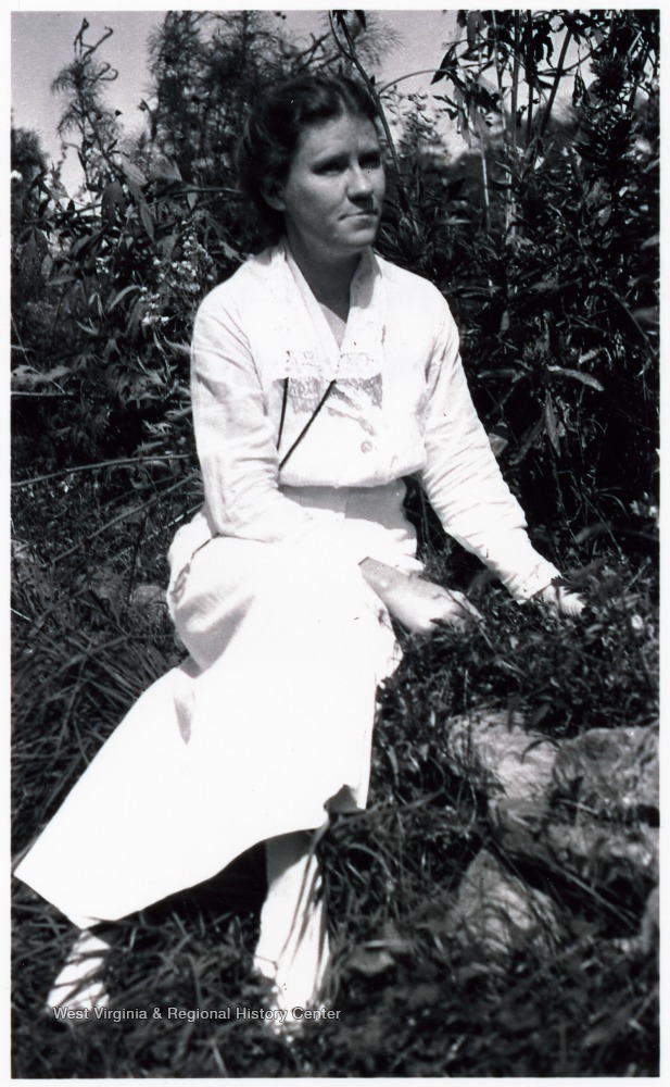 Margaret Prescott Montague in white dress, seated amid foliage in the sunshine