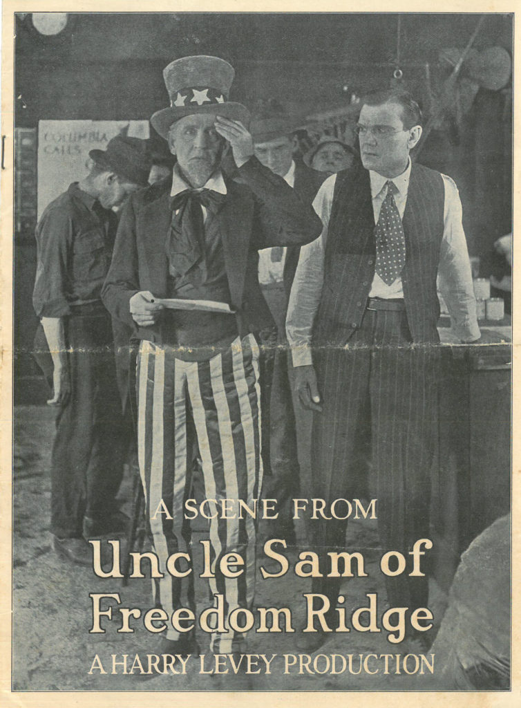 "Image of a man dressed as Uncle Sam holding a piece of paper, as another man in vest and tie looks on. Text says ""A Scene from Uncle Sam of Freedom Ridge A Harry Levey Production"""