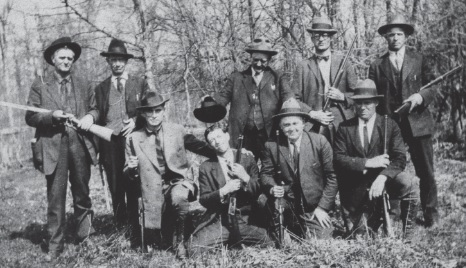 Group photo of men in suits, outdoors, most holding rifles or shotguns.
