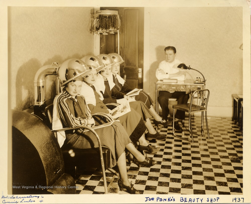 Four women under hairdryers in a salon as male staffer looks on