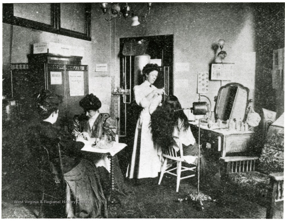 Woman dressing the hair of another woman, while another woman does the nails of a fourth woman.