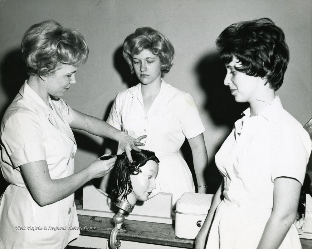Female student dresses the hair of a mannequin as two others look on.