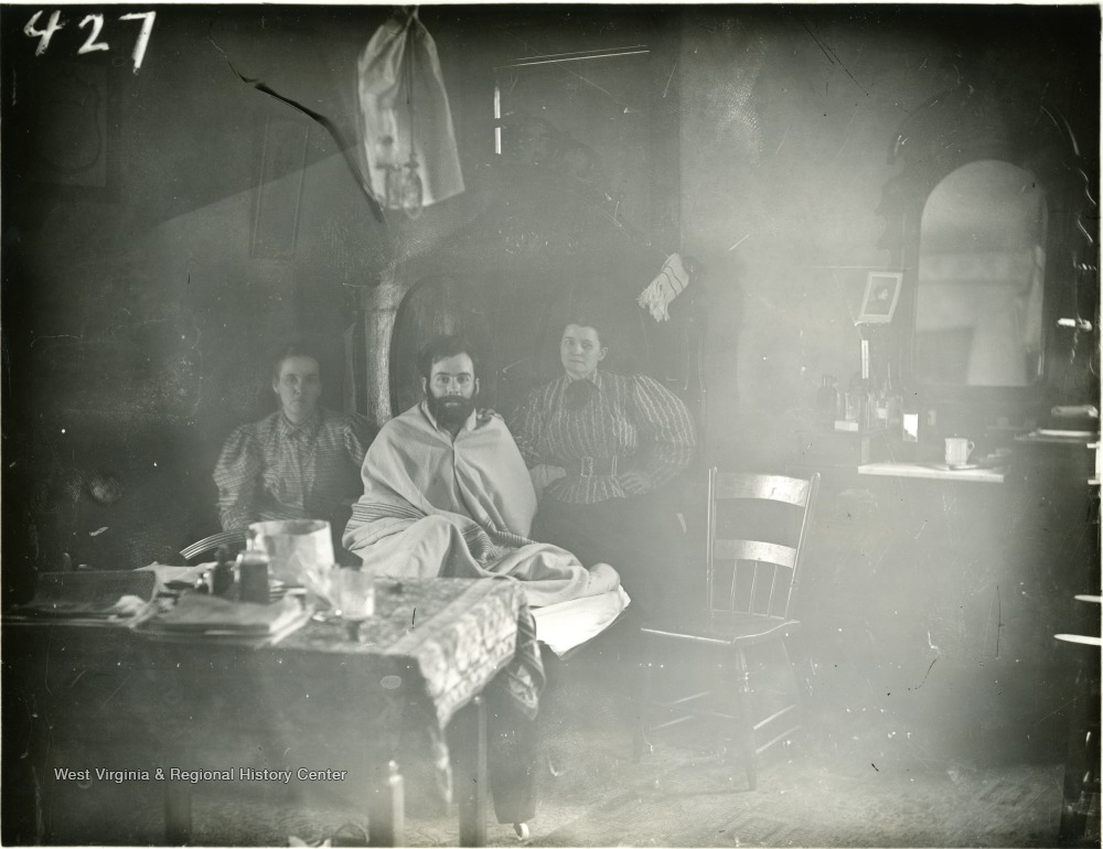 Seated man wrapped in sheet, awaiting haircut, between two women
