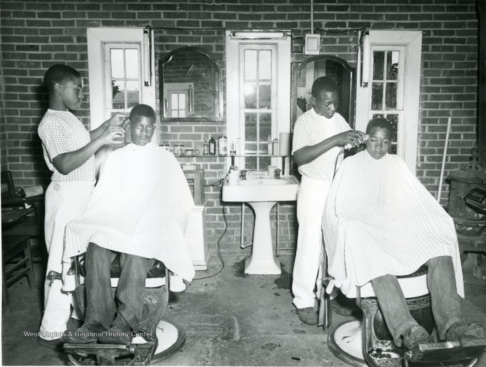 African-american boys giving each other haircuts inside a barbershop