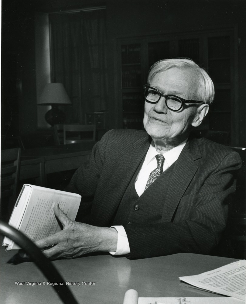 Oliver Chitwood as an older man, seated, holding a book