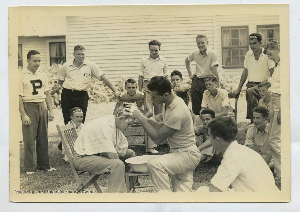 Man demonstrates washing a boy's hair over a bowl as group of boys watches outdoors