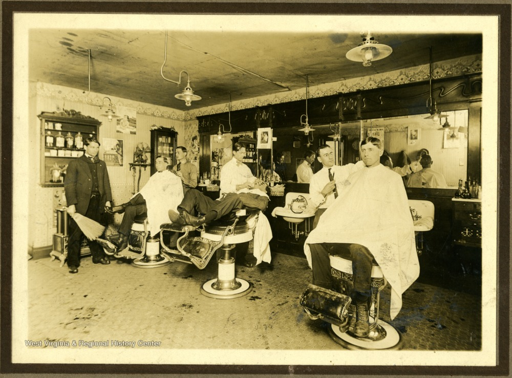 Interior of a barbershop full of barbers and customers