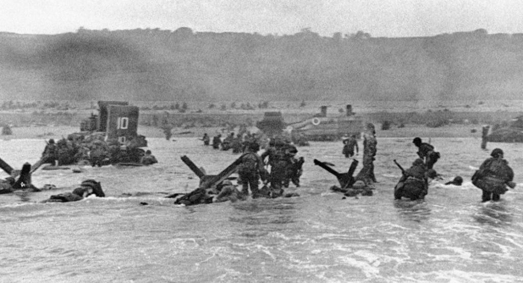 Photograph of soldiers in knee-deep water with heavy equipment, moving their way toward a beach