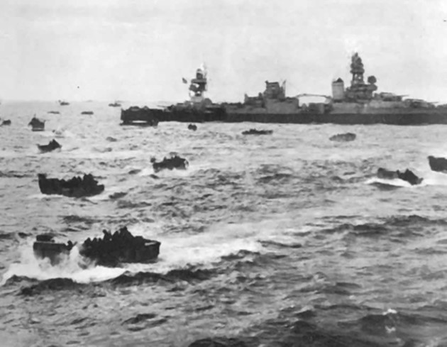 Photo of dozens of smaller boats full of people, with much larger naval vessel in the background