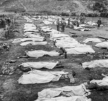 Photo of bodies laid out in rows and covered in white sheets, while a few people mill around