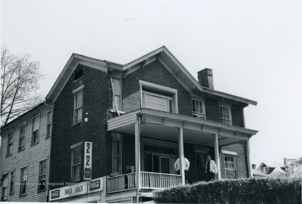 Black and white photo of a two story home, with two men on the front porch.