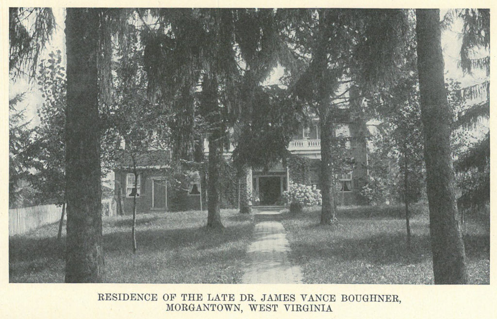 Black and white image of a home with many trees in the front yard