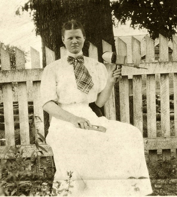Photo of woman seated outside, holding a stereoscope viewer