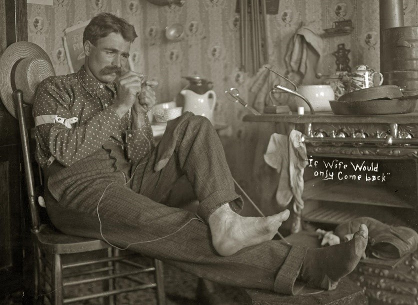 "Photo of man darning sock, with text ""If wife would only come back"""