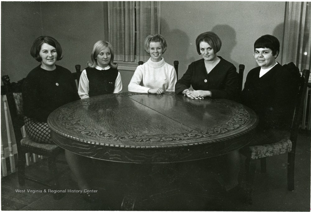 Portrait of five college aged women seated at a circular table