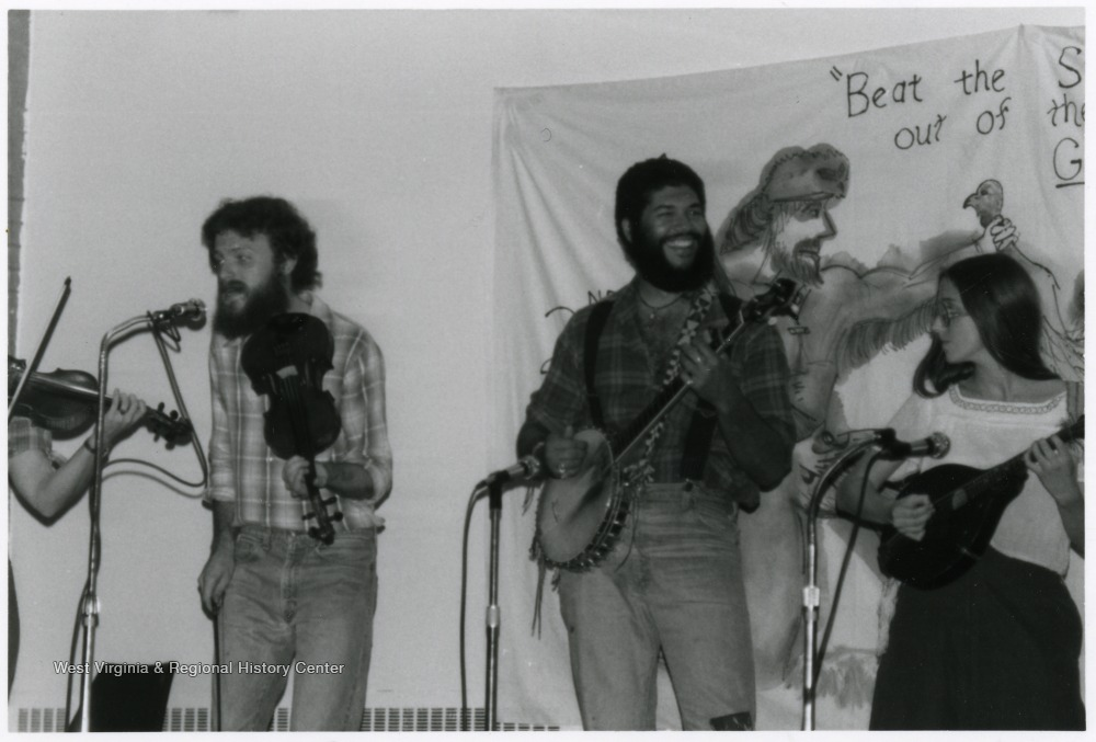 Fiddlers, banjo player, and mandolin player standing with microphones