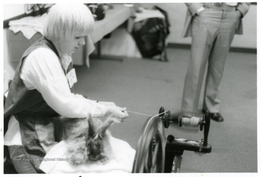 Person spinning yarn at a spinning wheel