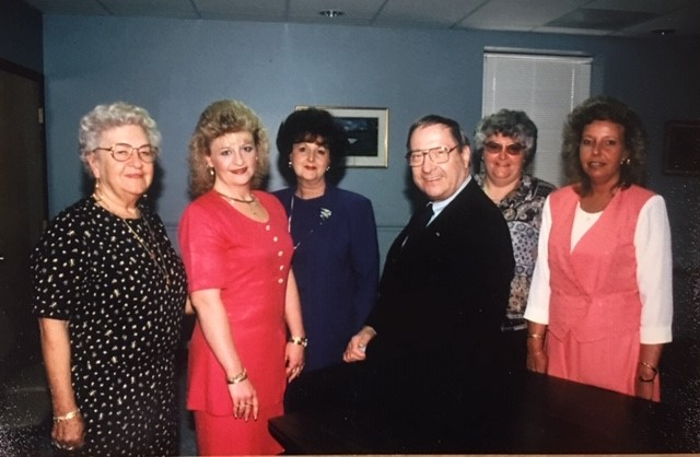 A man standing with five women