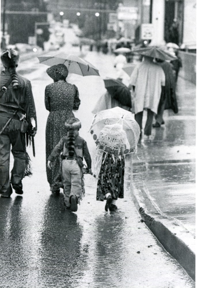 Family walking down a street in the rain, with the man and boy in Mountaineer costumes and the women in pioneer style dresses.