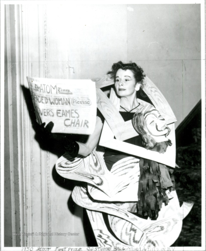 "Woman in costume made of frames and a paper mache head, holding newspaper, partly obscured, that reads, ""The Atom Times, __eaded woman (Picasso) ___overs Eames Chair"""